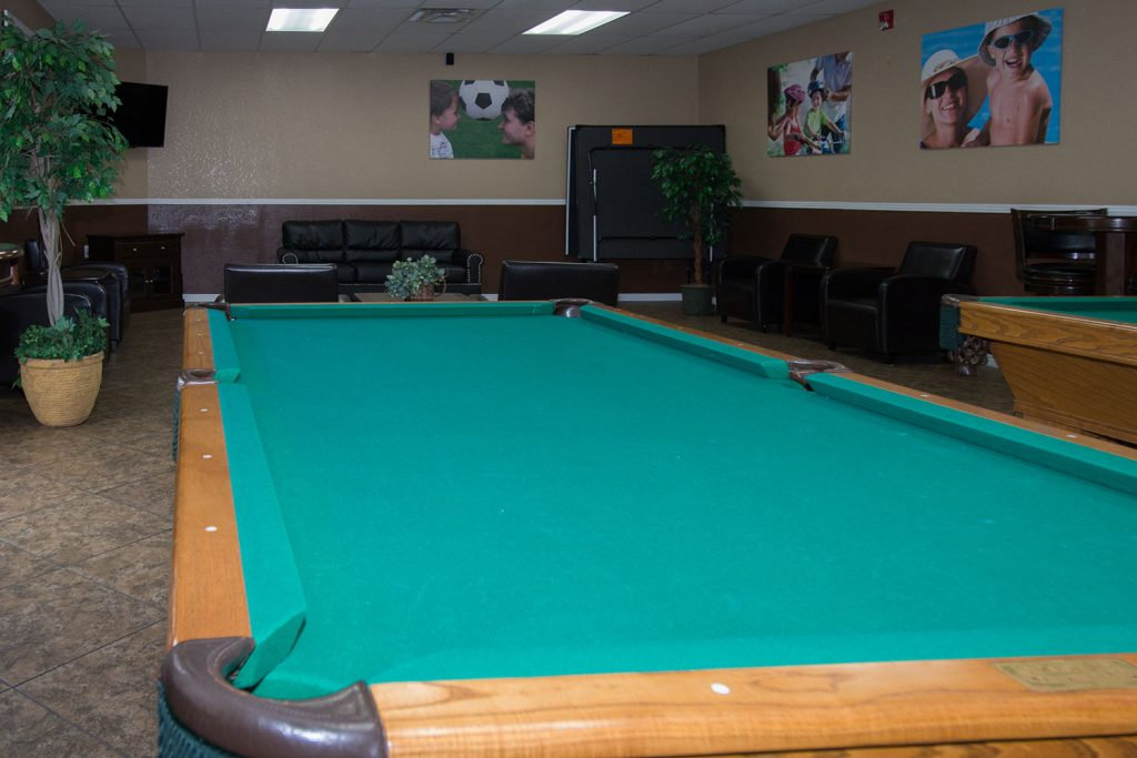 A billiards room with two pool tables. Pictures of families on the wall