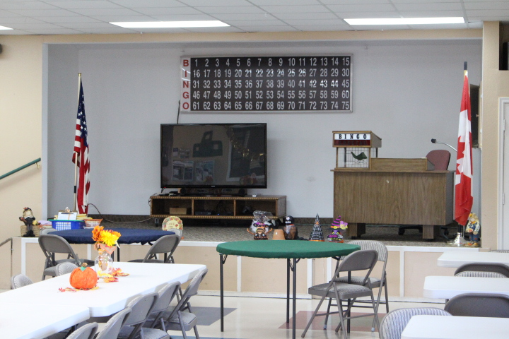 Clubhouse is set with long tables and chairs and a small stage for Bingo.
