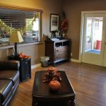 Office of Silver Spur Village decorated with autumn leaves and pumpkins. Leather loveseat, coffee table and area for coffee.