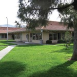 Southlake Mobiles community center, tree-lined and surrounded by luscious green grass. Well-maintained landscape and open walkways for easy access into the community center.
