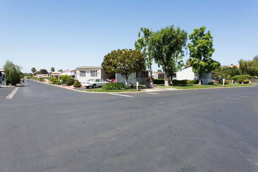 Wide corner street view within the senior community. Beautiful greenery line the streets with multiple manufactured homes.