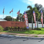 Village of Tampa, an all age manufactured home community's entrance is marked clearly with Flags that hover over the sign.