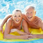 An active, mature man and woman enjoying the pool smiling away while on a yellow raft.
