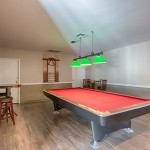 Pool table with bar stool and table seating.