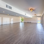 Beautiful hardwood floors and open space in the clubhouse with lots of natural light coming in due to a wall of windows.