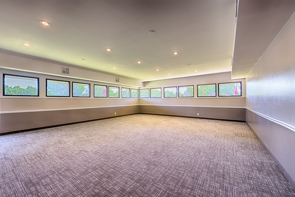 New carpeted meeting room with windows on 2 walls. Recessed lighting.