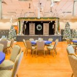 Ballroom decorated for a winder wonderland with 5 Christmas trees decorated in white, blue and green. Round tables decorated with blue tablecloth and white snowflakes and 8 chairs. A stage is decorated in Christmas theme with a blue, green white wreath. White stars also hang from the ceiling.