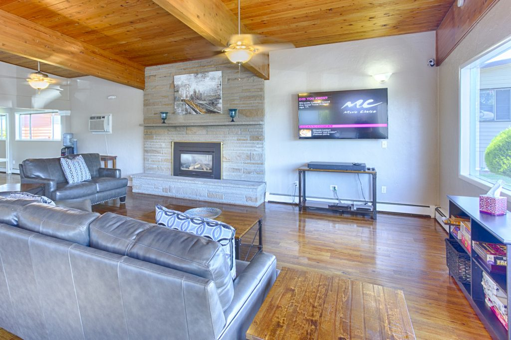 Modern and updated community center lounge. Beautiful, large stone fireplace and flat screen television make up the main wall. Light wood paneling on the high ceiling and matching wood, panel flooring create an open, cabin feel.