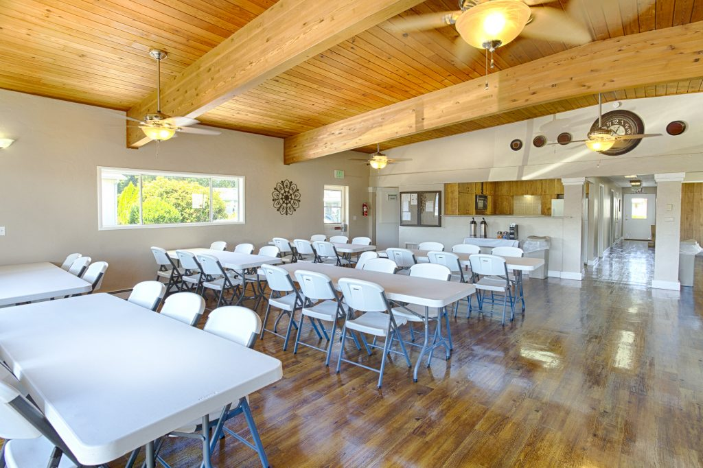 Open community center with high vaulted, wood ceilings and beautiful wood flooring. Spacious area for events. Long fold out tables and chairs make up majority of the space. Windows and ceiling fans with lights create a bright space.