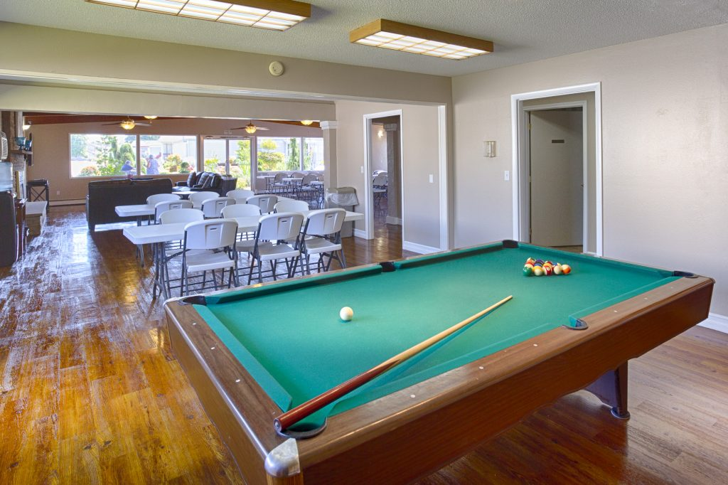 Community center equipped with a pool table and a variety of seating. Walls are lined with windows providing natural light.