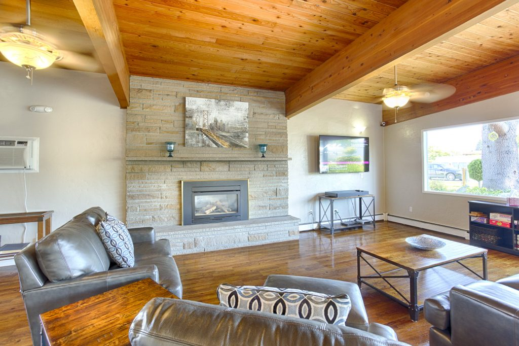 Beautiful, homey area in the community center with a flat screen television, beautiful, large, stone fireplace, and comfortable seating. High vaulted wood ceilings and matching wood flooring with a neutral, grey and black color scheme throughout.