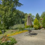 Outdoor area with a picnic table overlooking the Puyallup River. Beautiful view of river and luscious greenery.