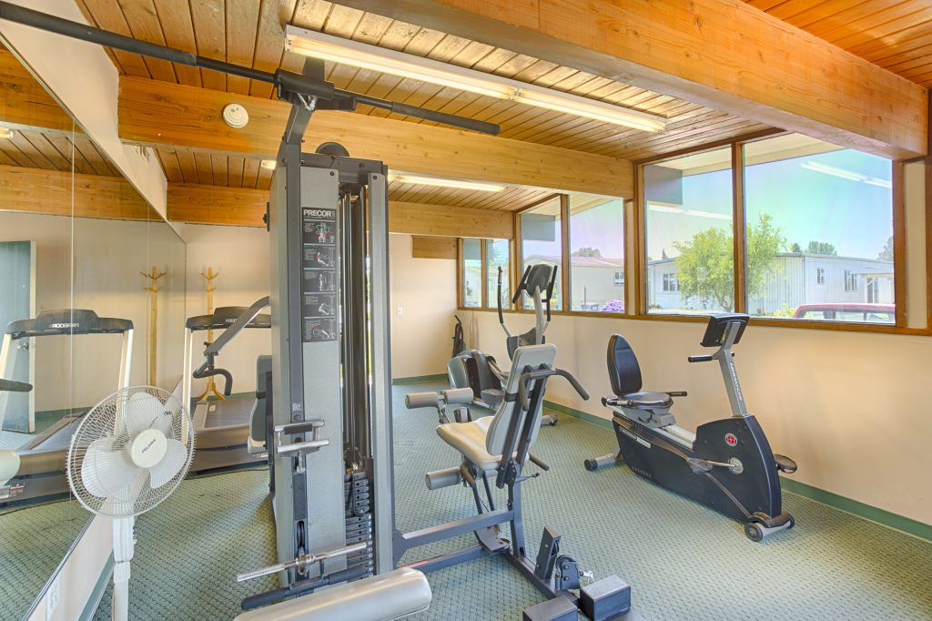 Indoor community gym equipped with a variety of workout equipment for residents use.