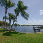 Green grass and palm trees lead up to the lake waters. Calm waters lap up to the docks.