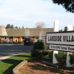 Entrance to Lakeside Village with white wood sign and brown lettering. In background is clubhouse.