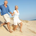 Senior Couple Enjoying Beach holding hands, running Down sand dune.