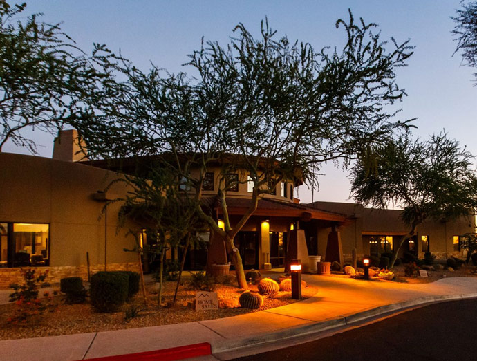 Montesa's office at dusk. Well lighted along pathway to front door. Homes sales sign placed out front by curb. tall Trees are planted along the pathway to front door.