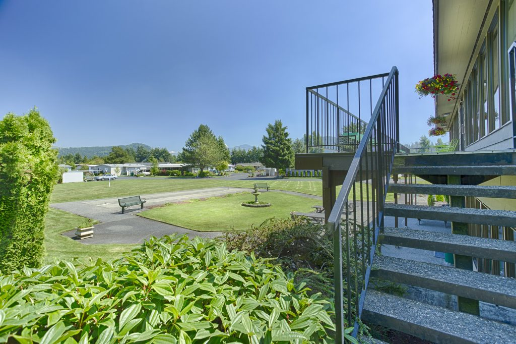 Open outdoor area with clean, cut grass, and well maintained landscape. Staircase leading up to the second level balcony of the community center.