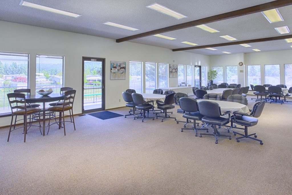 Open space community center enveloped by windows to enjoy natural light and the beauty of the outdoors. Equipped with circular tables surrounded by comfortable business chairs.