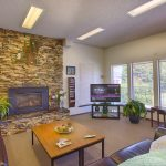 Tranquil community center with stone fireplace and flat screen television. Surrounded by brown leather couches for relaxation.