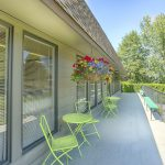 Long balcony outside the community center that overlooks the open outdoor area. Colorful flower bouquets hang from awning with bright green 3-piece seating sets are arranged below along the balcony.