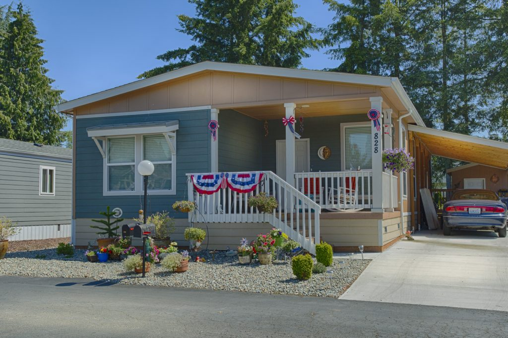 Beautiful manufactured home with small staircase leading up to covered porch. Painted with a shade of blue and decorated with an American flag theme. Side carport for one car coverage.