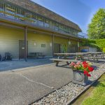 Outdoor picnic area just below the community center, overlooked by the balcony with access to the community center. Open picnic tables and grass area for events and social gatherings.