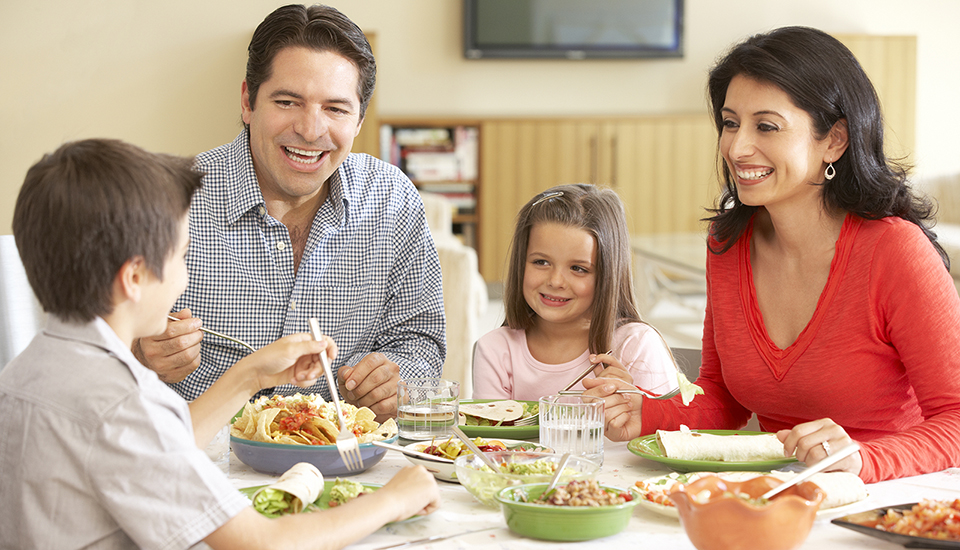 Northgate is an all age community where mother, father, son and daughter eat around the table smiling.