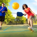 Retiree adult man and woman pickleball player in action. They are holding pickleball paddles posing to return the ball in a pickleball court.