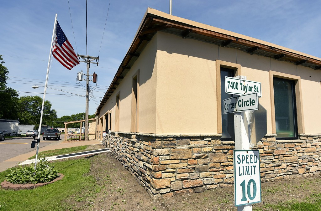 The clubhouse sits on the corner of 7400 Taylor St and Center Circle. An American flag flies high on the flag pole.