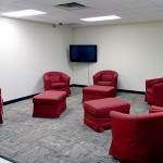 Game room with plush seating and tv mounted to wall for videos and movies.