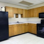 Full size kitchen with fridge, oven and microwave in the clubhouse. Brown kitchen cabinets for storage.