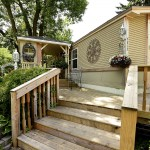 A manufactured home showcasing a beautiful wooden porch with Gazebo and hanging plants and lush tall green trees.