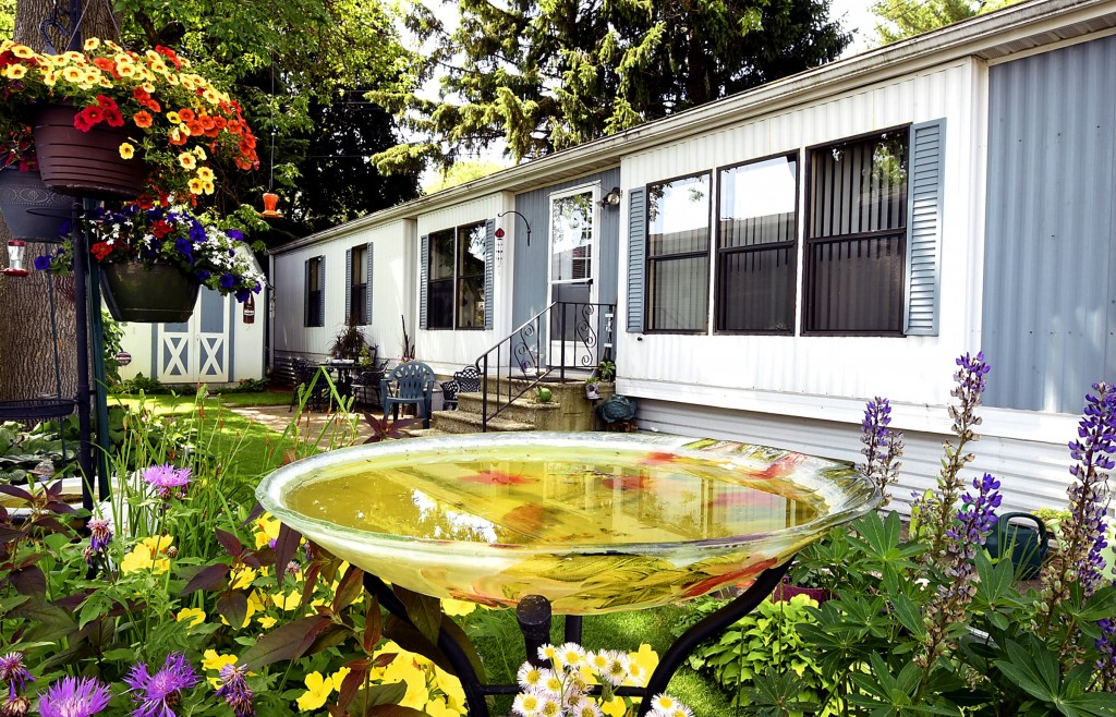 This home has lush landscape all around the outside. Vibrant yellow and red hanging flower plants, beautiful purple and yellow plants and a large fish bowl that has fish in it. Lush greenery all around.