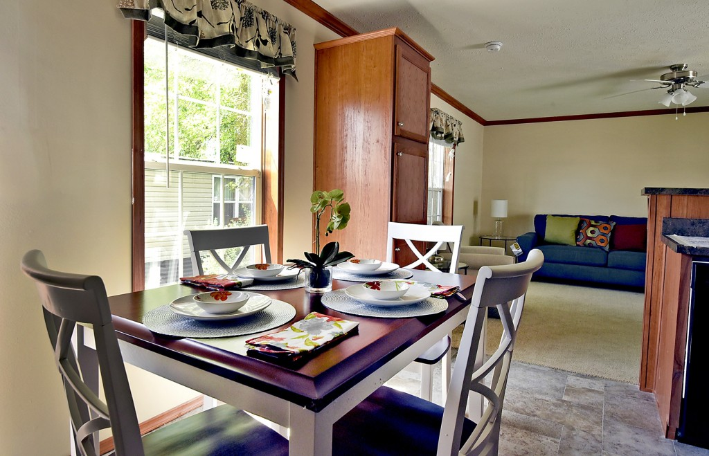 An open floor plan has large living area and a dining room. A kitchen table is set for four with chairs and dinnerware. Kitchen and dining room have beautiful tile throughout. Large living area is carpeted.