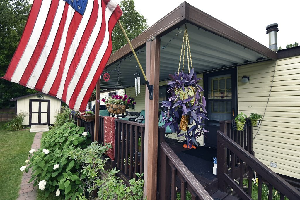A resident proudly displays the American flag from their front porch/ Lush landscaping with 2 hanging flower pots. One with beautiful purple flowers. Small shed in the back.