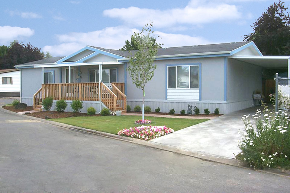 A well kept manufactured home with covered carport. Front porch covered. Bunch of pink, white, red flowers in grass at end of driveway. Small tree in front yard.