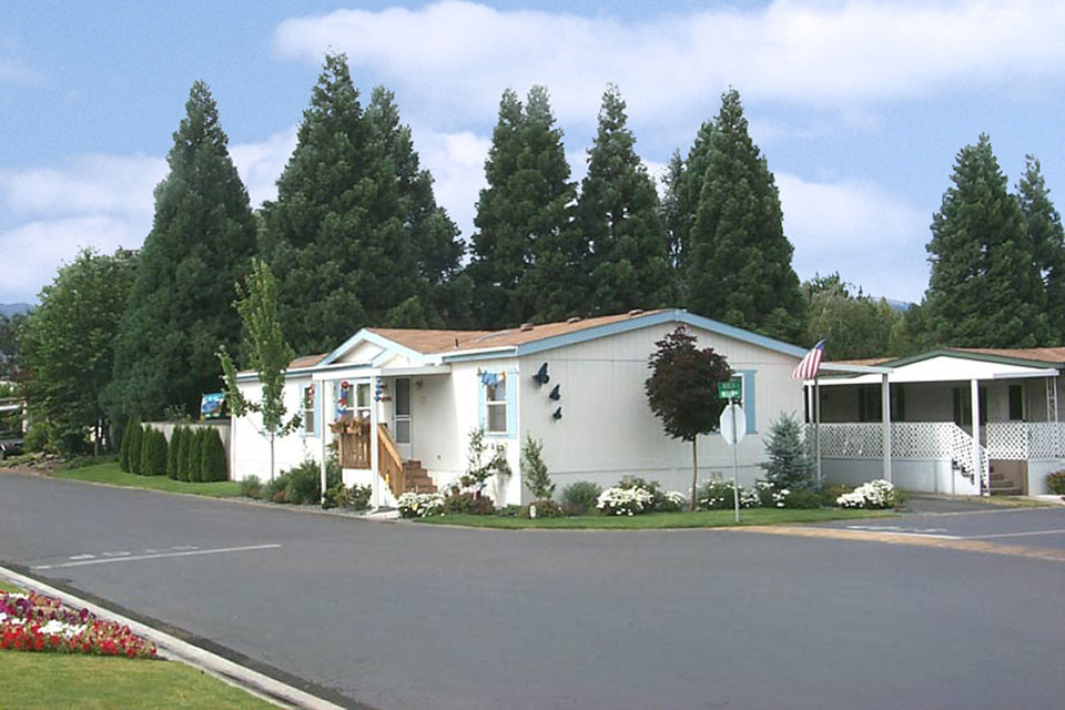 Clean paved streets and tall lush green trees surround manufactured homes.