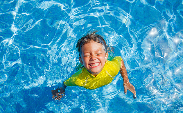 Happy boy in swimming pool with big smile, teeth showing, eyes closed. Wearing yellow swim top.