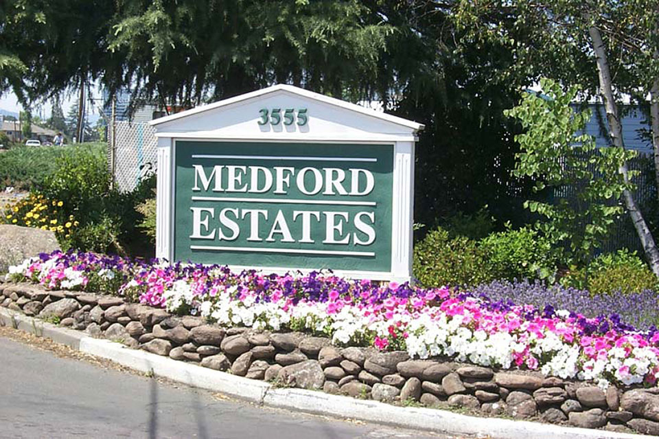 Medford Estates sign at entrance with purple, pink, white flowers planted in front of sign.