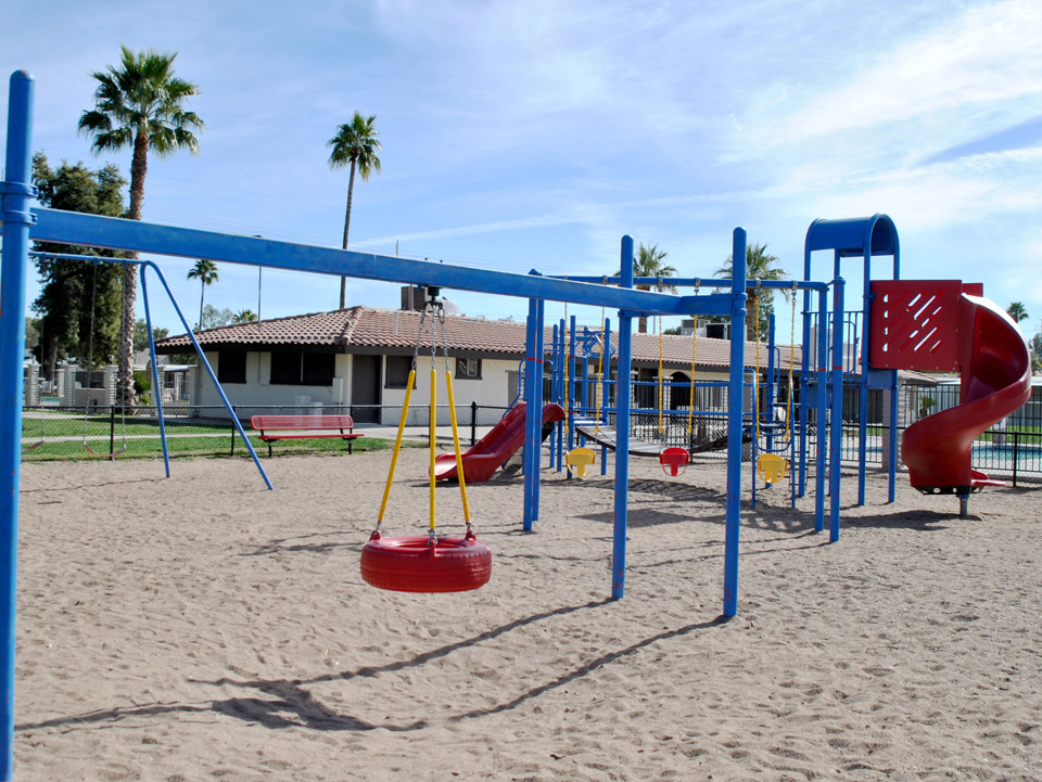 A playground colored with blue, yellow and red has swings, two slides, and a tire swing.