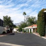 A quiet, peaceful, clean neighborhood with shade trees and mountains as the background.