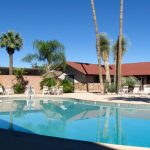 Far Horizons East in Tucson Arizona is an active 55 plus manufactured home community has pools with plenty of lounge chairs and tables with umbrellas for the hot desert days.