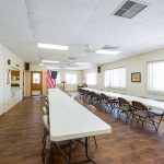 Bingo room equipped with two long tables and fold out chairs for multiple residents to take part in at a time.
