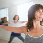 Portrait of beautiful older woman doing the warrior pose during yoga class.