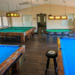 Game room with multiple billiard tables and a poker table. Hanging lights sit above each table.