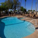 Large community pool with attached spa under the blue skies. Enclosed by black fencing and palm trees.