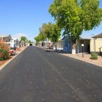 Large paved road surrounded by multiple, beautiful manufactured homes and greenery.