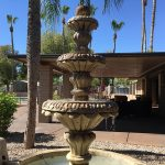 Pueblo Grande has a working water fountain with tall palm trees surrounding the area.