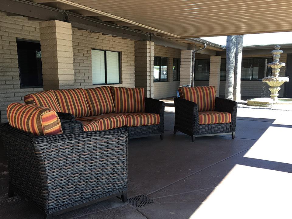 Wicker chairs with orange and brown stripes sit outside patio under awning and near water fountain.